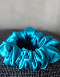 Blue Colored Silk Scrunchie Kept On A Grey Colored Fabric