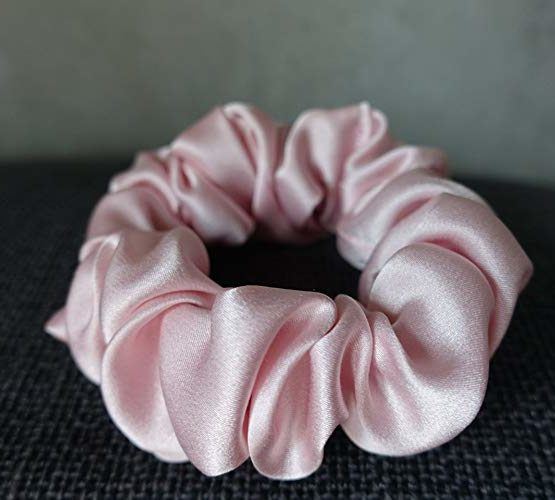 Pink Colored Silk Scrunchie Kept On A Grey Colored Fabric