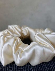 White Colored Silk Scrunchie Kept On A Grey Colored Fabric